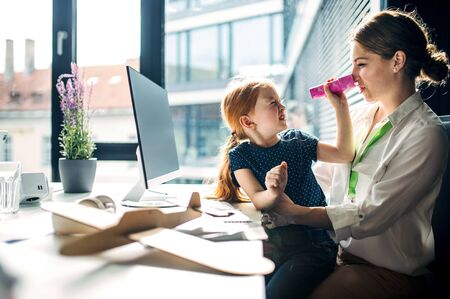A businesswoman with small daughter sitting in an office, working.