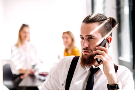 A portrait of young businessman with smartphone in an office, making call. Stockfoto