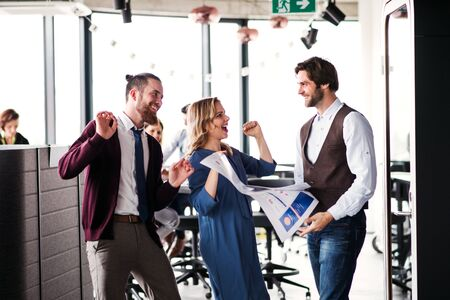 A group of business people standing in an office, expressing excitement. Stockfoto
