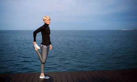 Side view portrait of young sportswoman standing outdoors on beach, stretching. Stockfoto