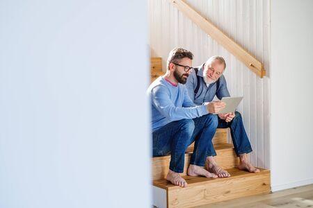 Un hijo adulto y un padre mayor con tableta sentado en las escaleras en el interior de su casa.