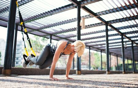 A young sportswoman doing exercise with TRX fitness straps outdoors. Stockfoto