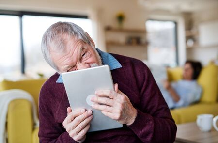 Senior man with tablet indoors at home, making funny faces. Stockfoto