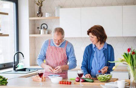 Un retrato de una pareja mayor en el interior de su casa, cocinando. Foto de archivo