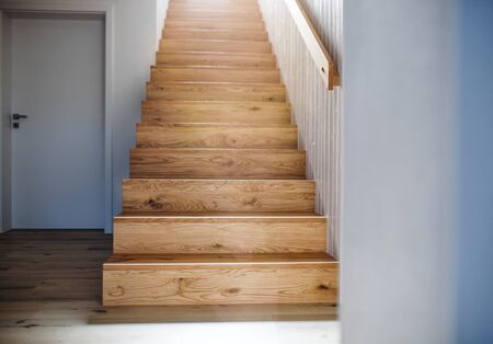 A wooden staircase and white wall in an interior of a house. Stockfoto