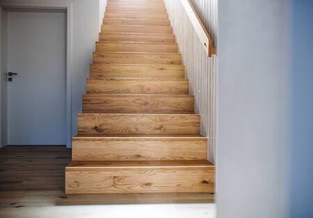 Drewniane schody i biała ściana we wnętrzu domu.