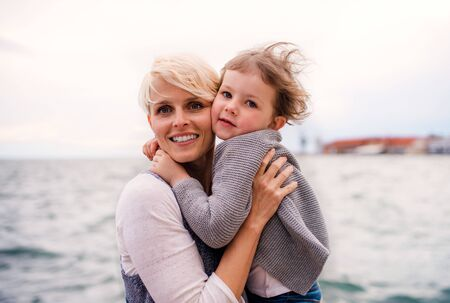 Young mother with small daughter standing outdoors on beach.