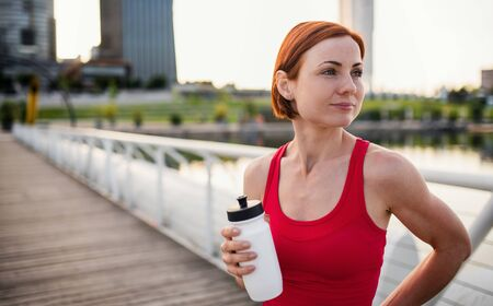 Young woman runner with water bottle in city, resting. Copy space. Stock Photo