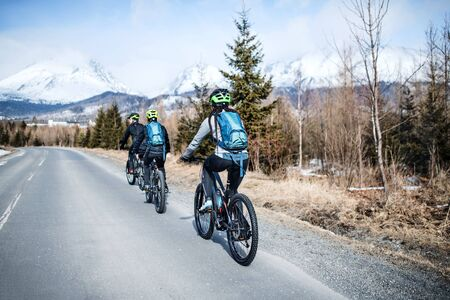 Rear view of group of mountain bikers riding on road outdoors in winter. Фото со стока