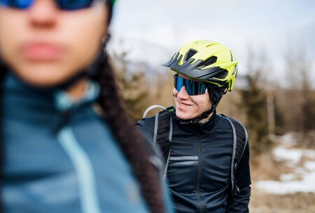 Two mountain bikers standing on road outdoors in winter.