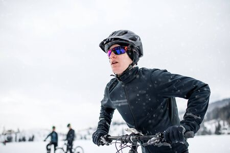 Side view of mountain biker riding in snow outdoors in winter nature.
