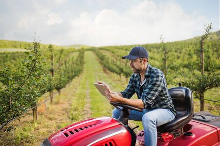A mature farmer with tablet sitting on mini tractor outdoors in orchard.