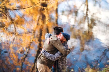 Senior father and his son standing in nature, hugging.