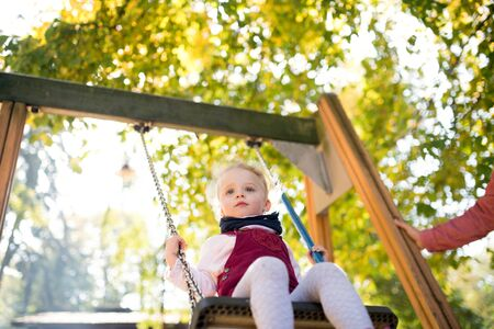 A small toddler girl with unrecognizable father on a swing on a playground.