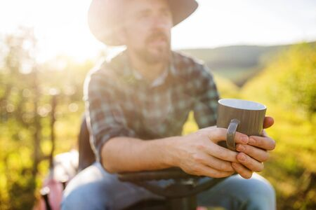 A mature farmer with cup of coffee outdoors in orchard, resting.