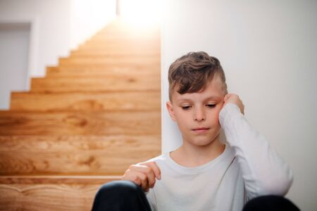 A small unhappy boy sitting on the floor by the stairs. Stock Photo