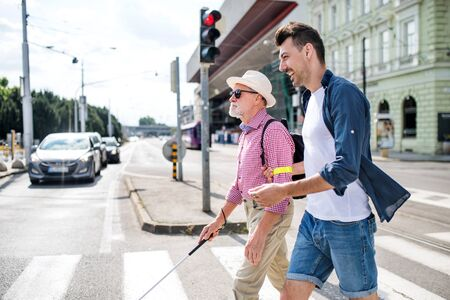 Young man and blind senior with white cane walking in city, crossing street. 写真素材