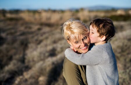 Young mother with small daughter in mediterranean nature, kissing.