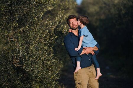 Father with small daughter standing outdoors by olive tree, kissing. Reklamní fotografie - 130626116