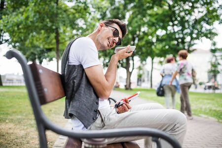 Young blind man with smartphone sitting on bench in park in city.