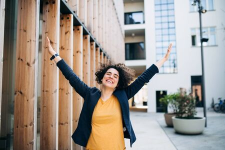A young businesswoman standing outdoors, expressing excitement. Reklamní fotografie