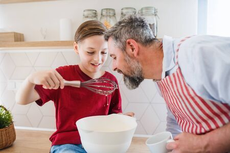 Matured father with small son in kitchen, making pancakes.