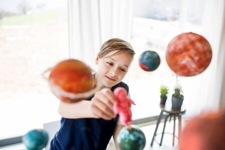 A small boy with model of solar system indoors.