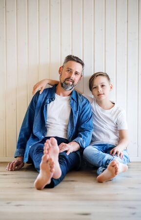 Reifer Vater mit kleinem Sohn, der drinnen sitzt und die Kamera betrachtet.