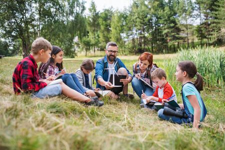 Group of school children with teacher and windmill model on field trip in nature. Zdjęcie Seryjne