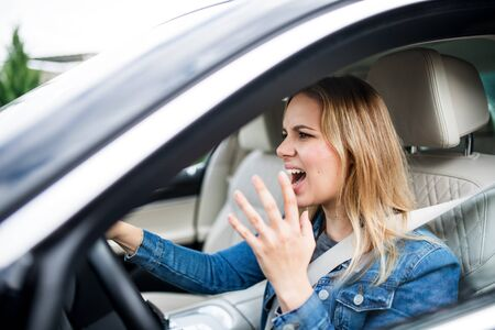 Angry young woman driver sitting in car, shouting.