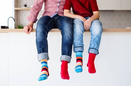 Midsection of father with son with funky socks sitting on kitchen counter indoors.
