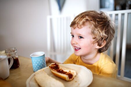 A front view of a toddler boy eating at home.