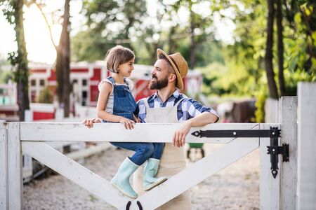 A portrait of father with small daughter outdoors on family farm.