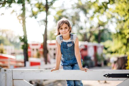 A portrait of small girl on family farm, standing on wooden gate.