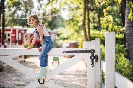 A portrait of small girl on family farm, sitting on wooden gate.