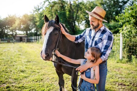 Mature father and small daughter with horse working on small family animal farm. Фото со стока
