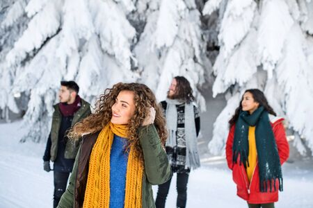 A group of young friends on a walk outdoors in snow in winter forest.