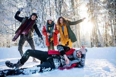 Group of young friends on a walk outdoors in snow in winter forest, having fun. 免版税图像