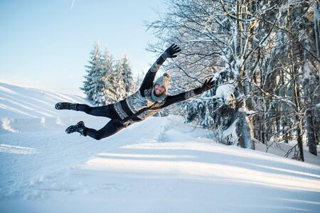 Young man having fun in snow outdoors in winter, jumping.