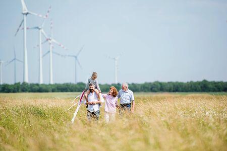 Multigeneration family walking on field on wind farm. Reklamní fotografie
