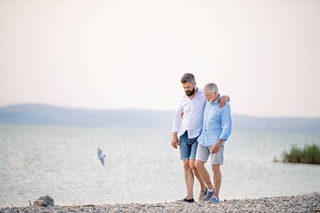 Senior father and mature son walking by the lake. Copy space.