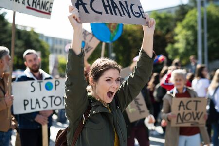 Young woman with placard and poster on global strike for climate change.