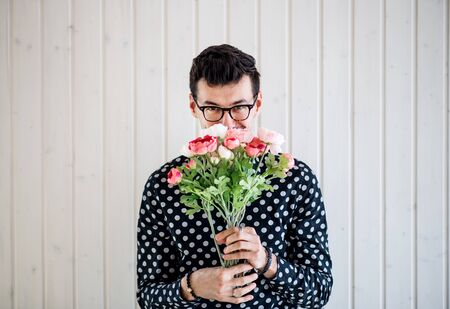 Young man with flowers standing against white wooden background wall.