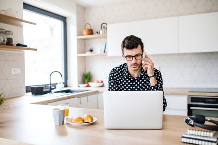 Young man with laptop and smartphone sitting in kitchen, a home office concept. Фото со стока