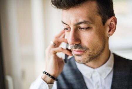 Young man with smartphone standing indoors at home, making a phone call.