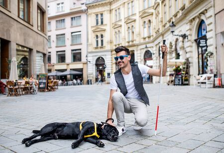 Young blind man with white cane and guide dog on pedestrian zone in city.