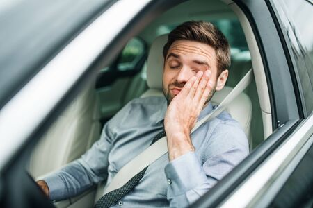 Young bored business man with shirt and tie sitting in car.