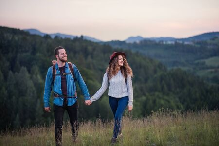 Young tourist couple travellers with backpacks hiking in nature.