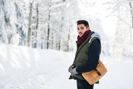 Young man standing outdoors in snow in winter forest, looking at camera.