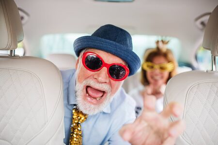Cheerful senior couple with party accessories sitting in car, having fun.